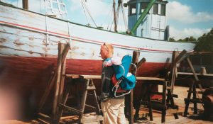 Dänemark Mann mit kind in der Kraxe vor einem Boot im Museum