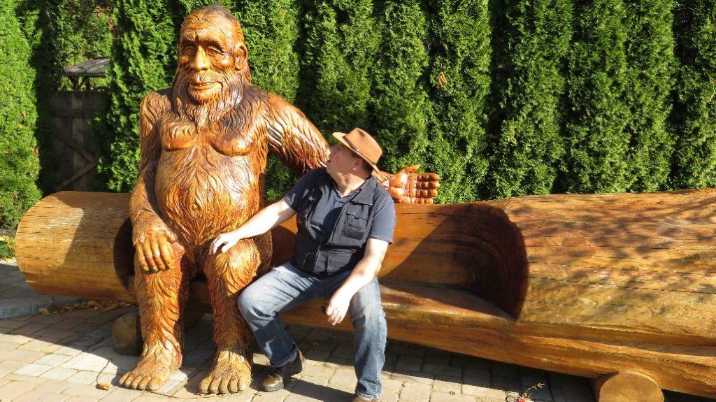 Mann sitzt neben Holzbigfoot auf der Bank Vancouver Fraser valley