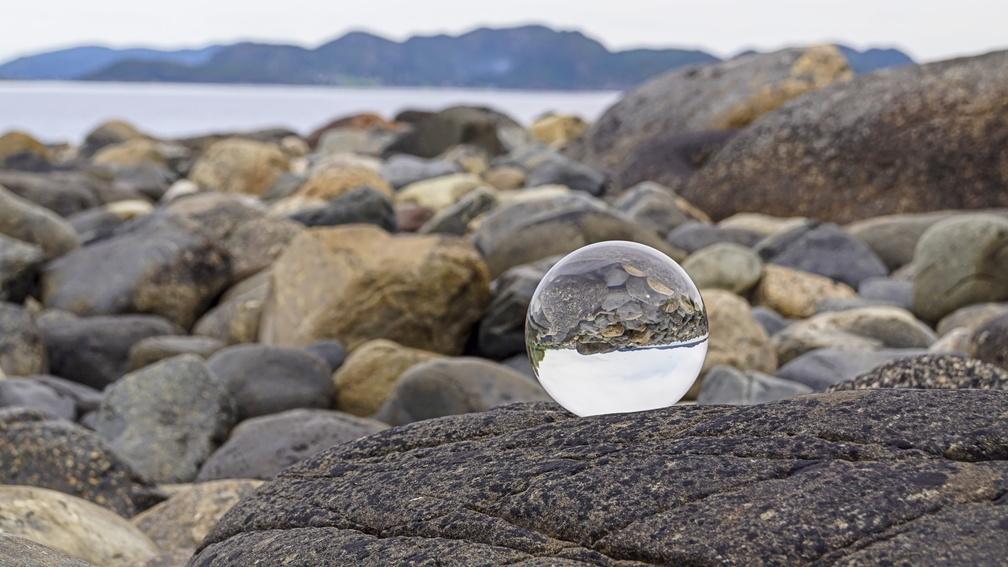 Glaskugel an einem steinigen Strand