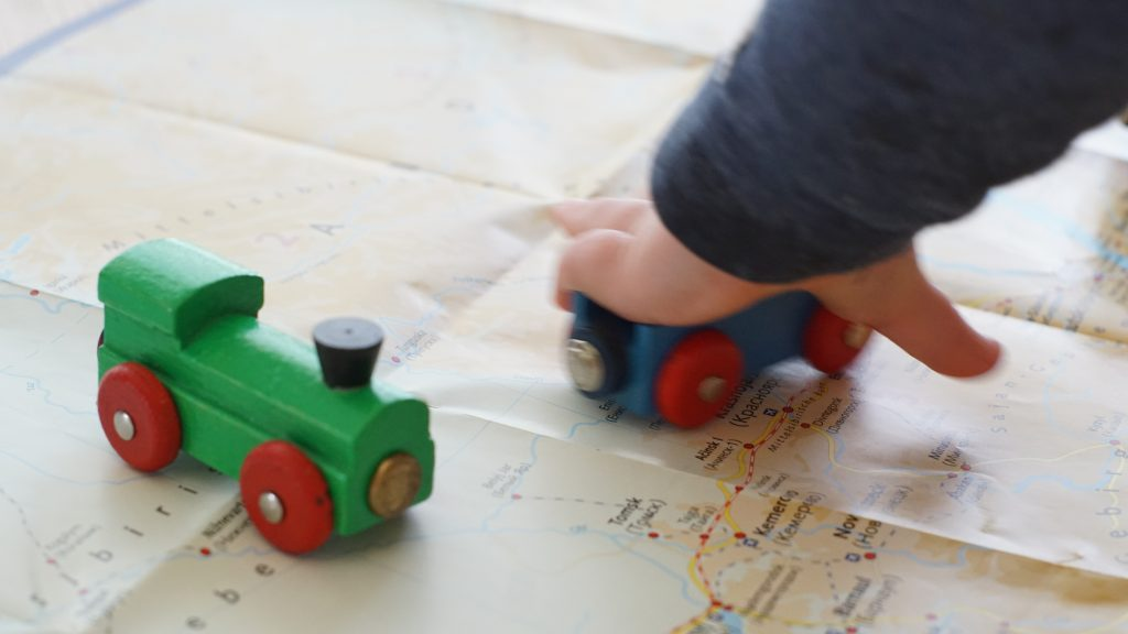 Spielzeug lok auf landkarte mit kinderhand