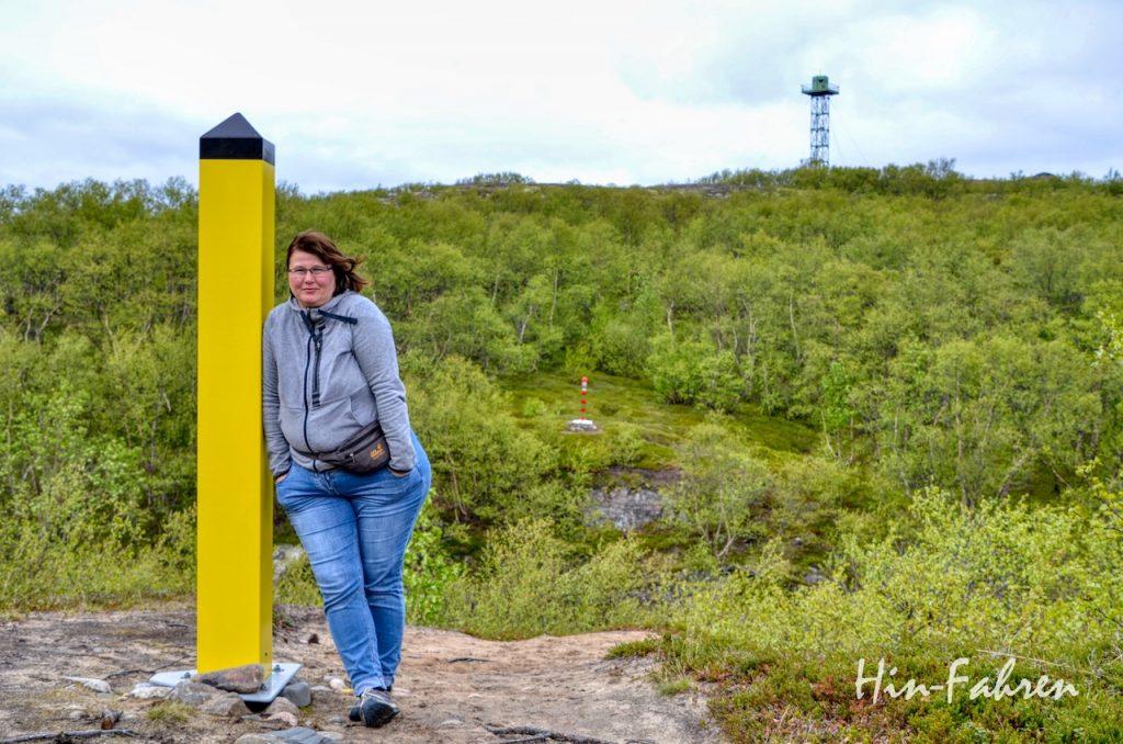 Frau an Grenzstein in Hammerfest