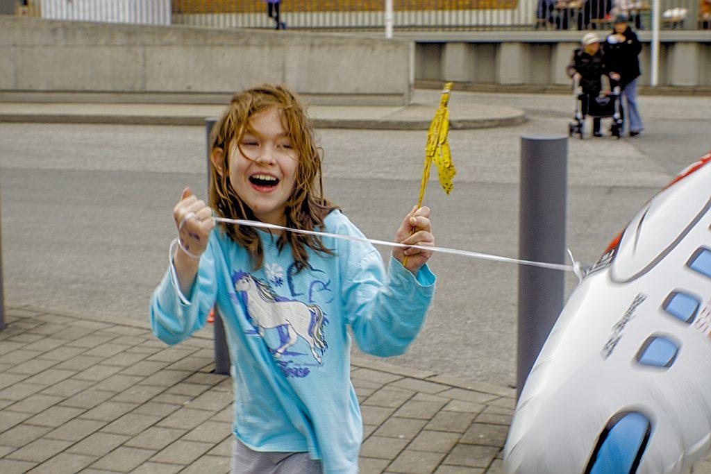 Kind mit Luftballon Sturm Spass