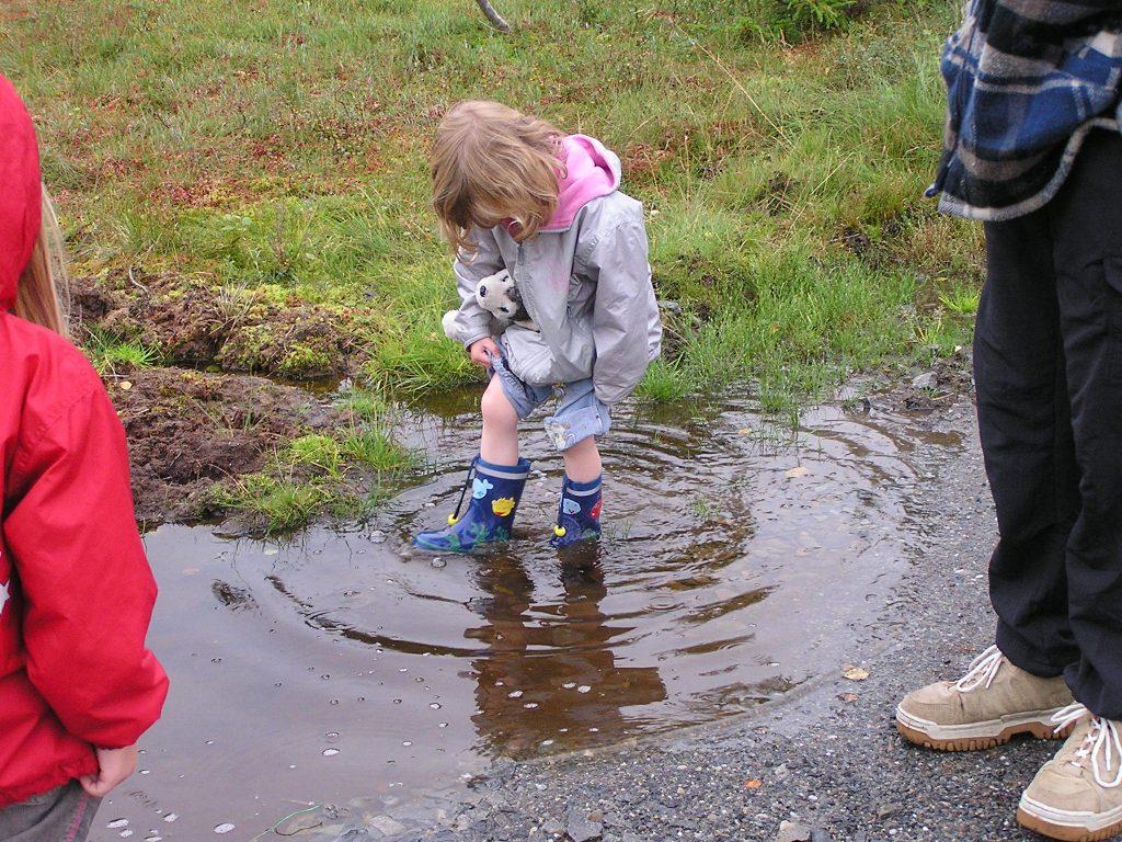 Regen, Kind in Pfütze Norwegen Jøssåsen landsbyauswandern nach norwegen